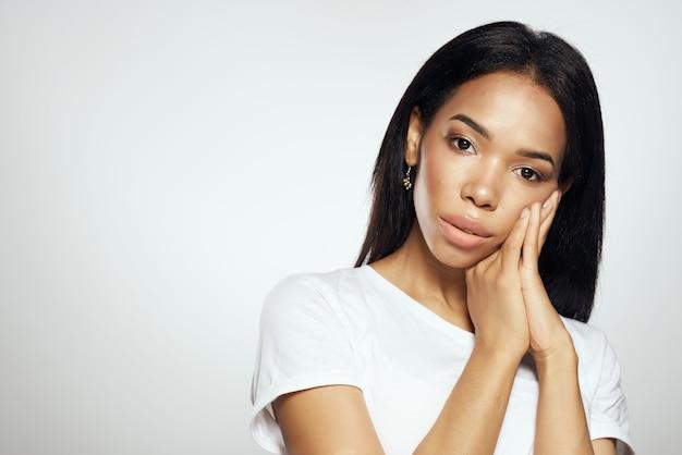 Mulher atraente de aparência africana com uma camiseta branca ajeita os brincos de cabelo