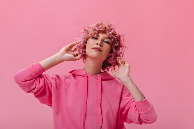 Mulher atraente de cabelo rosa com capuz fúcsia olhando para a frente no isolado
