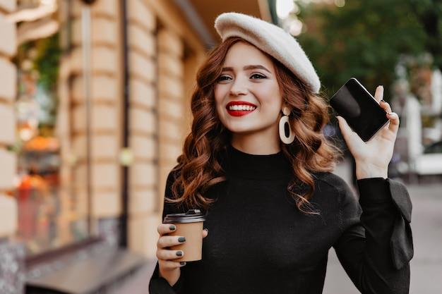 Mulher atraente de cabelos compridos na boina posando durante a caminhada. tiro ao ar livre da menina bonita ruiva com uma xícara de café e telefone.