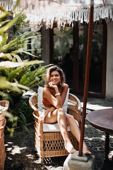 Mulher atraente de cabelos curtos em um top marrom sorrindo e olhando para a frente em um jardim aconchegante