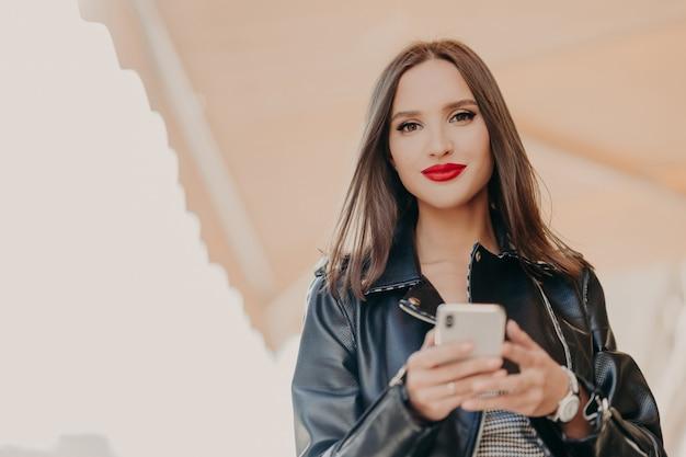 Mulher atraente de cabelos escura com lábios pintados de vermelhos, vestida de jaqueta de couro preta, segura o celular moderno