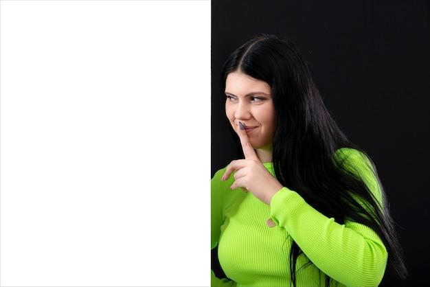 Mulher atraente de cabelos escuros com roupas de cores brilhantes e um pôster branco em branco, isolado em um fundo escuro