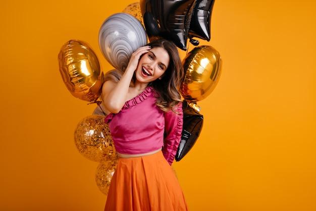 Mulher atraente de cabelos escuros comemorando aniversário