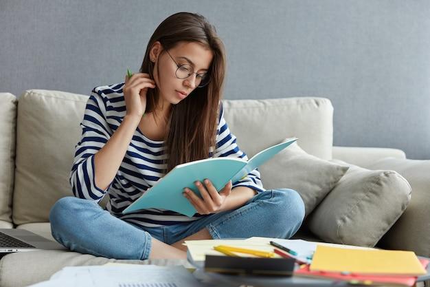 Mulher atraente de cabelos escuros lendo um livro, cercada de papéis, segura uma caneta
