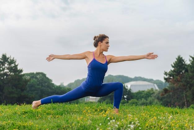 Mulher atraente de cabelos escuros trabalhando em sua flexibilidade enquanto pratica ioga na natureza