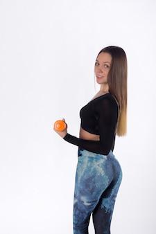 Mulher atraente de esportes posa com halteres em estúdio, fundo branco