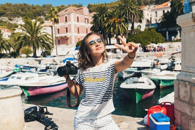 Mulher atraente de férias na europa à beira-mar em um cruzeiro tirando fotos para a câmera