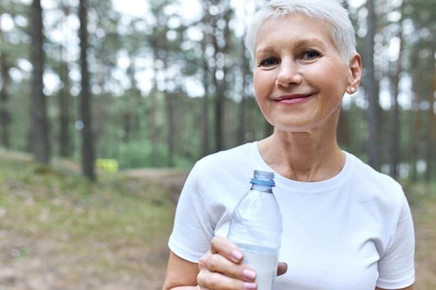 Mulher atraente de meia idade, cabelo curto, camiseta branca, posando ao ar livre com pinheiros