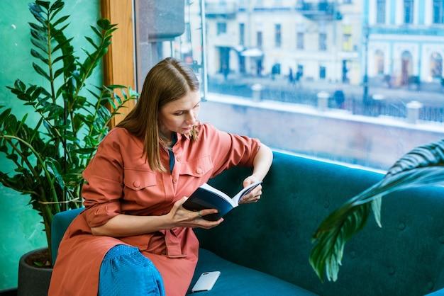 Mulher atraente de meia idade, desfrutando de ler um livro sentado no sofá na sala de estar, sorrindo enquanto ...