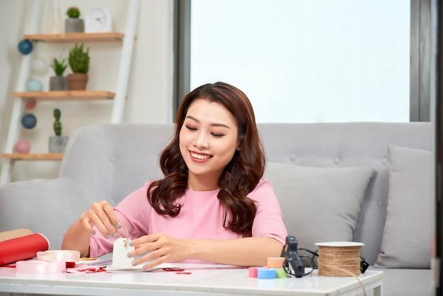 Mulher atraente de meia-idade fazendo scrapbook em casa