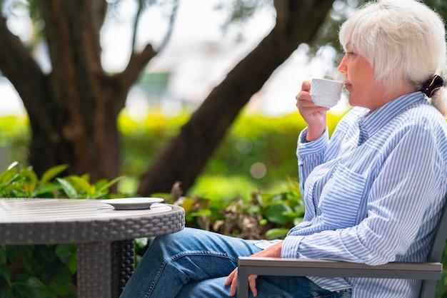 Mulher atraente de meia-idade na moda relaxando com uma xícara de café