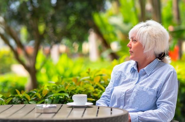 Mulher atraente de meia idade relaxando em um pátio ao ar livre