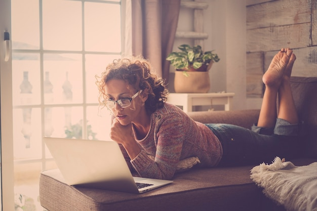 Mulher atraente de meia-idade usando tecnologia de laptop de internet em casa