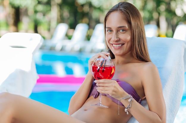 Mulher atraente de olhos azuis usando pulseiras elegantes e um suco de fruta refrescante