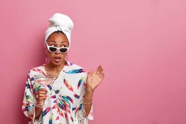 Mulher atraente de pele escura e saudável olha de lado surpreendentemente, bebe coquetel, usa roupão de seda e toalha enrolada, óculos escuros, fica de pé contra a parede rosa, espaço de cópia