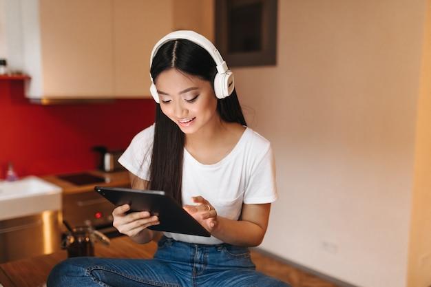 Mulher atraente de top branco curtindo música em fones de ouvido e segurando o tablet enquanto está sentado na cozinha