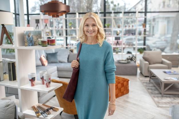 Mulher atraente de vestido azul caminhando pelo salão de móveis, onde há muitas coisas para o interior, sorrindo.