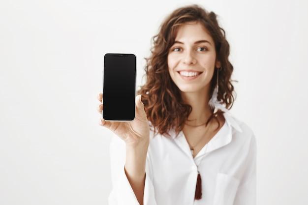 Mulher atraente demonstrando aplicativo na tela do smartphone