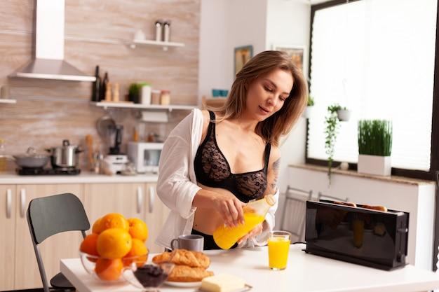 Mulher atraente derramando suco durante o café da manhã usando lingerie sexy. jovem mulher sexy e sedutora com tatuagens bebendo suco de laranja caseiro e saudável, refrescante domingo de manhã