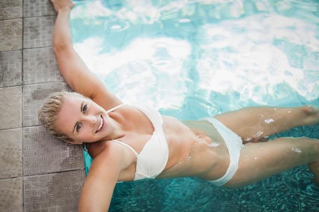 Mulher atraente, descansando na beira da piscina
