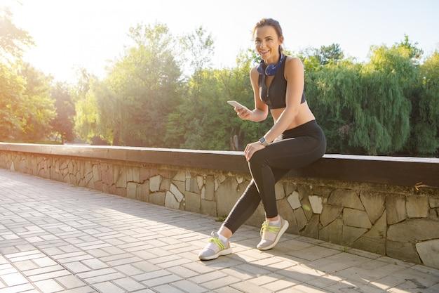 Mulher atraente desportiva usando smartphone com fones de ouvido no parque de manhã