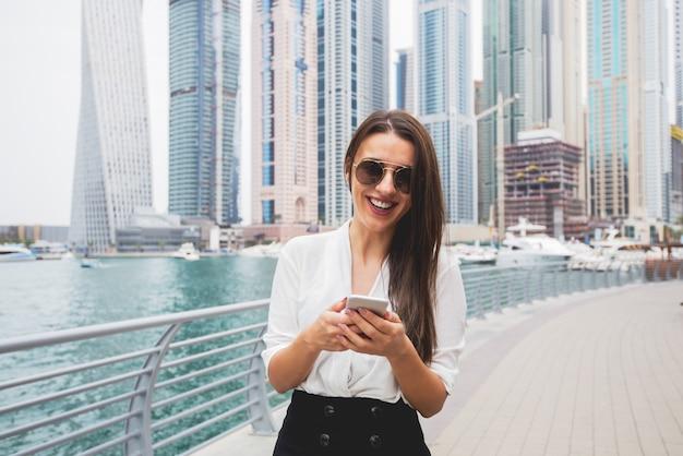 Mulher atraente digitando no telefone inteligente, olhando para a câmera sorrindo. vista panorâmica do espaço bela cidade ao fundo.