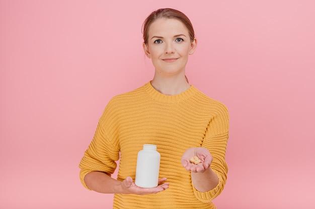Mulher atraente dona de casa segura um tubo com vitaminas e dá os comprimidos para alguém
