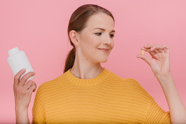 Mulher atraente dona de casa segurando um tubo com vitaminas e pronta para comer um comprimido