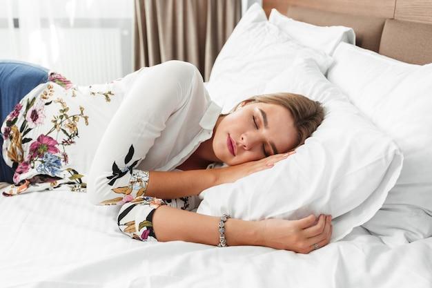 Mulher atraente dormindo na cama em um quarto de hotel