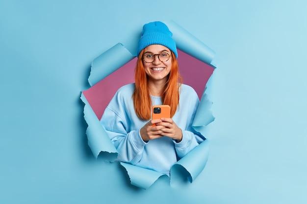 Mulher atraente e alegre com cabelo vermelho contém mensagens de texto de tipos de smartphones modernos, gosta de navegar nas redes sociais, usa chapéu azul e macacão.