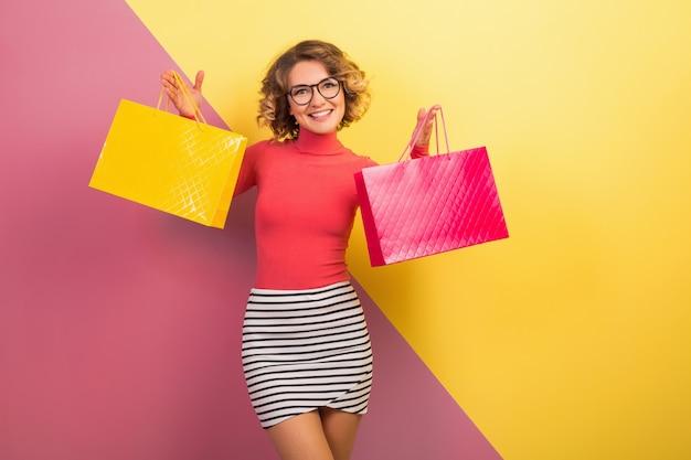 Mulher atraente e animada sorridente com roupa colorida elegante segurando sacolas de compras no fundo rosa amarelo, shopaholic à venda, tendência da moda verão