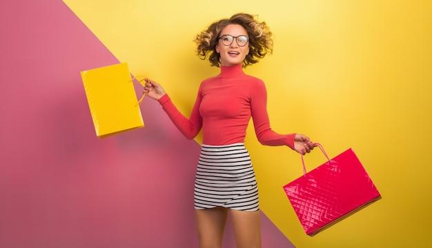 Mulher atraente e animada sorridente em roupa colorida elegante segurando sacolas de compras