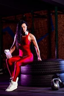 Mulher atraente e apta com agitador posando em um grande pneu no ginásio.