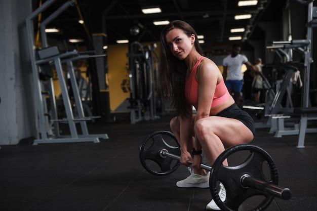 Mulher atraente e atlética fazendo levantamento terra com barra, copie o espaço Foto Premium