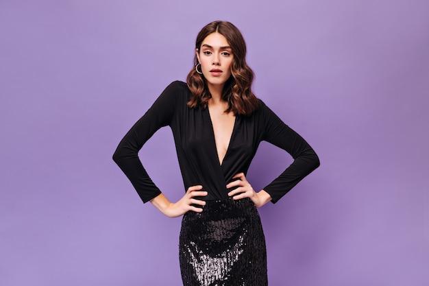 Mulher atraente e cacheada em um vestido preto festivo posa na parede roxa