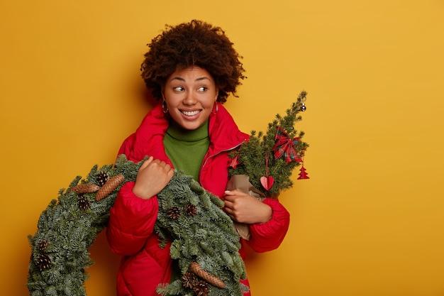 Mulher atraente e cacheada sorri com os dentes, olha para o lado, vestida com agasalhos, segura uma pequena árvore de abeto decorada e coroa de abetos