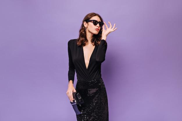 Mulher atraente e cacheada usando óculos escuros
