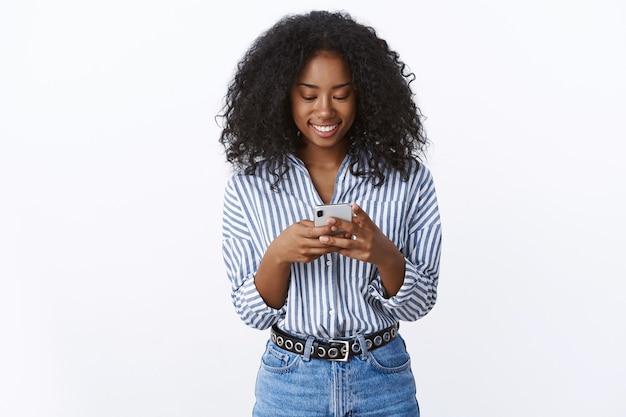 Mulher atraente e charmosa de pele escura, cabelos cacheados, usando smartphone, sorrindo, sorrindo alegremente, conversa agradável on-line, encontrando um aplicativo de namoro de pares amorosos, de pé em uma parede branca alegre e animada
