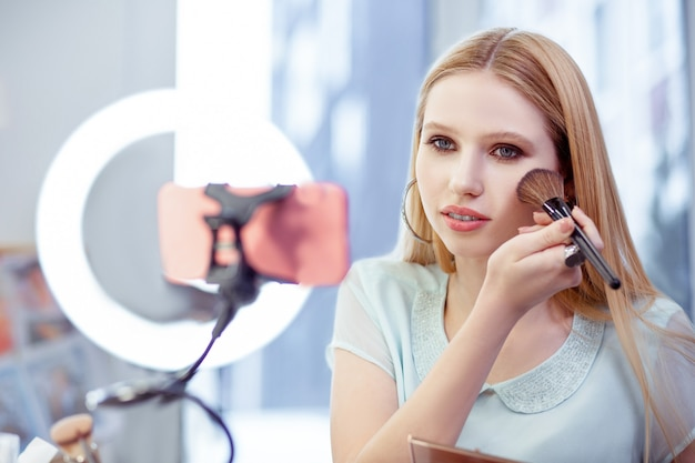 Mulher atraente e charmosa sentada na frente de seu smartphone enquanto grava um vídeo para seu blog