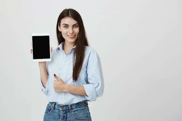 Mulher atraente e confiante com o polegar para cima mostrando a tela do tablet digital