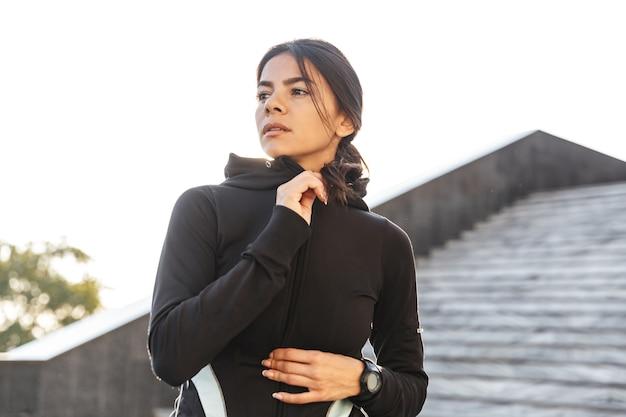 Mulher atraente e confiante em fitness vestindo roupas esportivas, fazendo exercícios ao ar livre, posando