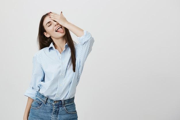 Mulher atraente e despreocupada cobrindo um olho e mostrando a língua