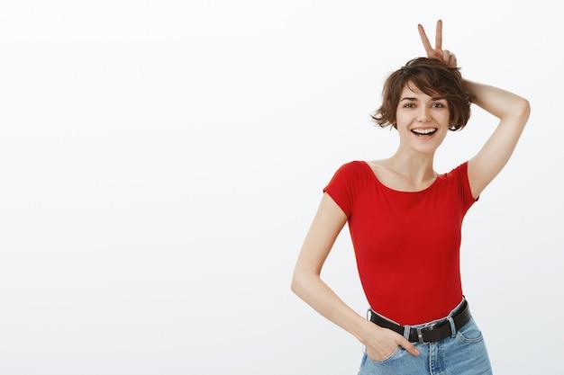 Mulher atraente e despreocupada mostrando o gesto de orelhas de coelho acima da cabeça e rindo feliz