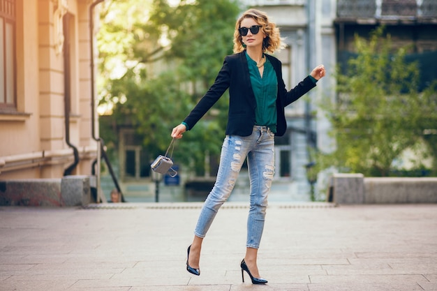 Mulher atraente e elegante andando na rua da cidade com sapatos de salto alto, vestindo calça jeans, jaqueta preta, blusa verde, óculos escuros, segurando uma bolsa pequena, tendência da moda do verão, bela senhora magro