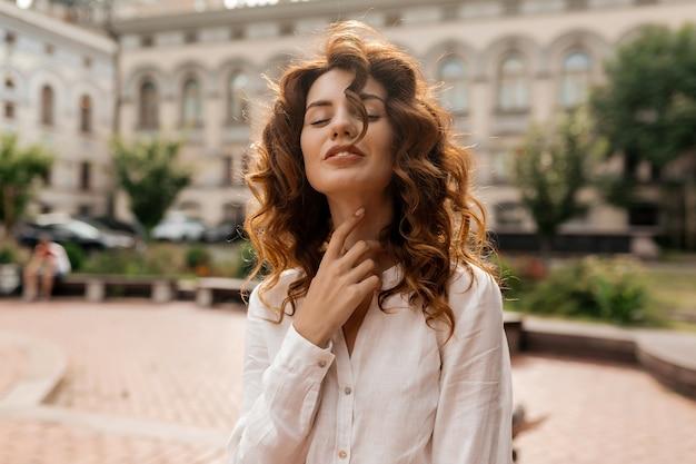 Mulher atraente e elegante com cabelo ruivo cacheado vestida de camisa branca tocando seu pescoço com os olhos fechados e sorrindo