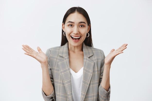 Mulher atraente e elegante com jaqueta e brincos redondos, gesticulando com as palmas das mãos e sorrindo