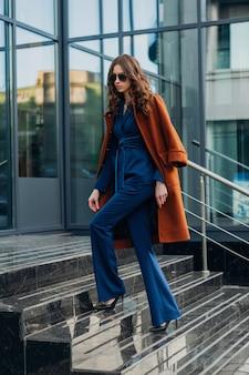 Mulher atraente e elegante com uma caminhada na rua comercial da cidade urbana, vestida com um casaco marrom quente e um terno azul, estilo de rua na moda primavera outono, usando óculos escuros