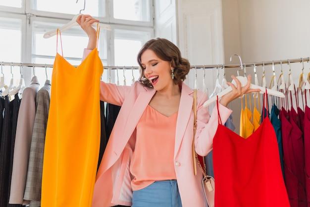 Mulher atraente e elegante e sorridente escolhendo roupas em loja de roupas