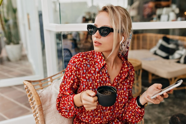 Mulher atraente e elegante em óculos de sol pretos, bebendo café e falando no smartphone