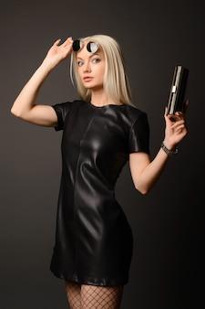 Mulher atraente e elegante em um vestido de couro preto com uma pequena bolsa prateada
